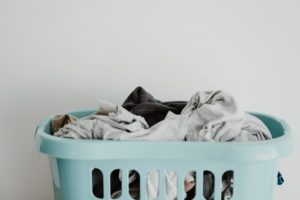 picture of an aqua colored laundry basket overflowing with clothes