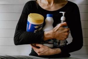 picture of the torso of a woman holding cleaning products