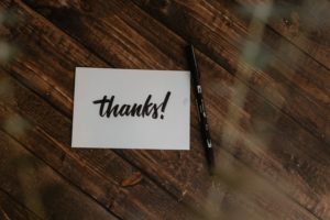 """picture of a thank you card that says """"thanks!"""" on a wood floor with a pen"""