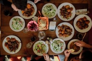 above photo of a table filled with food with multiple people eating
