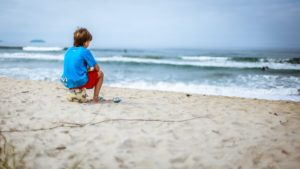 elementary school aged boy sitting on a soccer ball looking out into the ocean