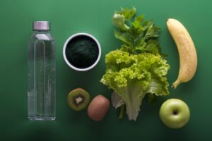flat lay picture of a water bottle and a variety of fruits and vegetables on a green background